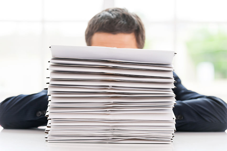 photo of a business man in Canada hiding behind a stack of papers for hiring employees for his business